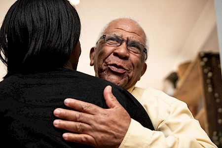 Older man hugging volunteer